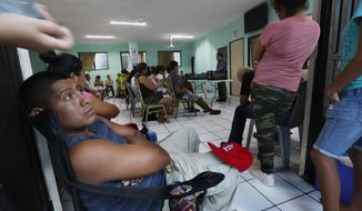 Pastor Aaron Mendes speaks to migrants staying at his AMAR migrant shelter in Nuevo Laredo, Mexico, Wednesday, July 17, 2019. Asylum-seekers grappled to understand what a new U.S. policy that all but eliminates refugee claims by Central Americans and many others meant for their bids to find a better life in America amid a chaos of rumors, confusion and fear. (AP Photo/Marco Ugarte)