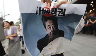 "In this Thursday, July 18, 2019, photo, a protester tries to tear a paper showing an image of Japanese Prime Minister Shinzo Abe during a rally denouncing the Japanese government's decision on their exports to South Korea in front of the Japanese embassy in Seoul, South Korea. South Korean police on Friday, July 19, say a man has set himself on fire in front of the Japanese Embassy in Seoul amid rising trade disputes between Seoul and Tokyo. The signs read ""Abe's government."" (AP Photo/Ahn Young-joon)"