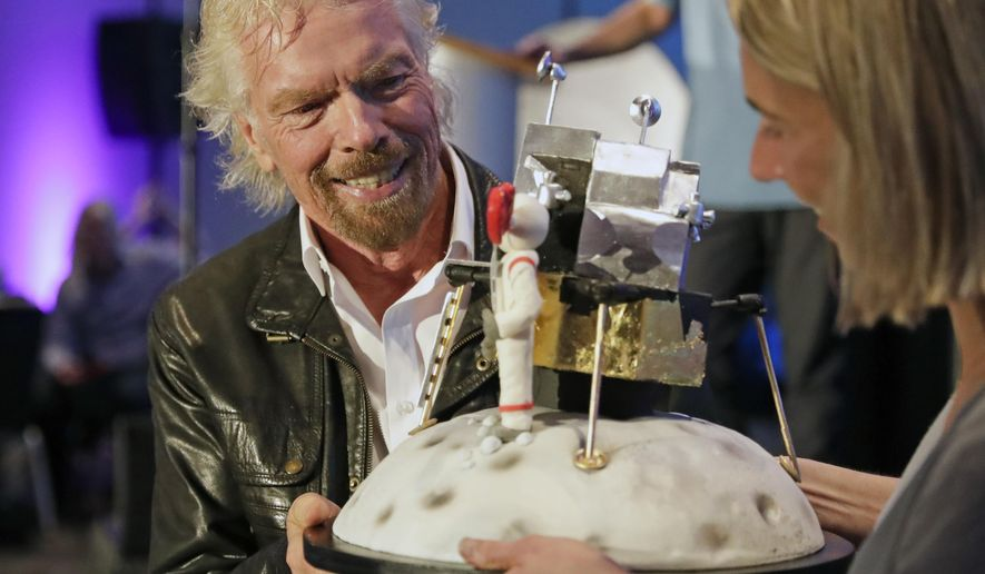 Richard Branson is presented with a space-themed cake during a luncheon attended by 100 Virgin Galactic ticket holders, to mark his 69th birthday and in recognition of the Apollo 11 moon landing anniversary at the Kennedy Space Center Visitor Complex, Thursday, July 18, 2019, in Cape Canaveral, Fla. (AP Photo/John Raoux)