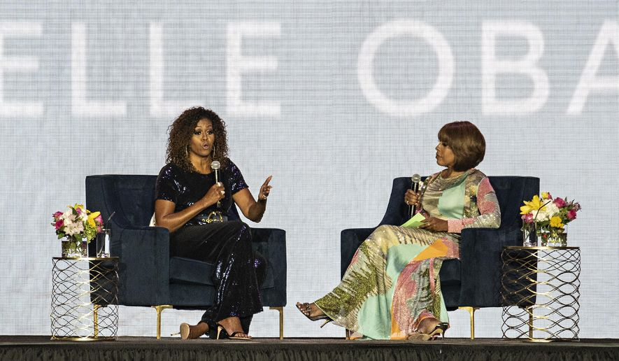 Michelle Obama, left, speaks as Gayle King listens during the 2019 Essence Festival at the Mercedes-Benz Superdome, Saturday, July 6, 2019, in New Orleans. (Photo by Amy Harris/Invision/AP)