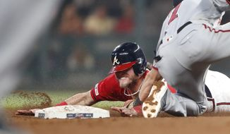 Atlanta Braves' Josh Donaldson, left, is tagged out by Washington Nationals shortstop Trea Turner as he tries to steal second base in the seventh inning of a baseball game Friday, July 19, 2019, in Atlanta. (AP Photo/John Bazemore)