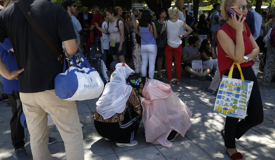 Tourist hug each other in Syntagma square after a strong earthquake hit near the Greek capital of Athens, Friday, July 19, 2019. The Athens Institute of Geodynamics gave the earthquake a preliminary magnitude of 5.1 but the U.S. Geological Survey gave it a preliminary magnitude of 5.3. The Athens Institute says the quake struck at 2:38 p.m. local time (1113 GMT) about 26 kilometers (13.7 miles) north of Athens. (AP Photo/Petros Giannakouris)