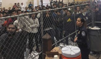 """Men stand in a U.S. Immigration and Border Enforcement detention center in McAllen, Texas, Friday, July 12, 2019, during a visit by Vice President Mike Pence. Acknowledging """"this is tough stuff,"""" Pence said he was not surprised by what he saw as he toured the McAllen Border Patrol station Friday where hundreds of men were kept in caged fences with no cots amid sweltering heat. (Josh Dawsey/The Washington Post via AP, Pool)"""