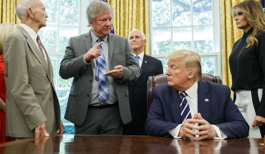 """President Donald Trump, accompanied by Apollo 11 astronaut Micheal Collins, left, Eric """"Rick"""" Armstrong, son of Neil Armstrong, second from left, with Vice President Mike Pence and first lady Melania Trump, listens during a photo opportunity commemorating the 50th anniversary of the Apollo 11 moon landing, in the Oval Office of the White House, Friday, July 19, 2019, in Washington. (AP Photo/Alex Brandon)"""