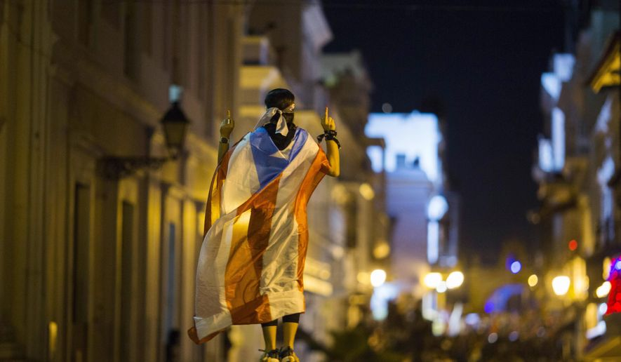 A demonstrator with a Puerto Rican flag reacts during clashes in San Juan, Puerto Rico, Wednesday, July 17, 2019. Thousands of people marched to the governor's residence in San Juan on Wednesday chanting demands for Gov. Ricardo Rossello to resign after the leak of online chats that show him making misogynistic slurs and mocking his constituents. (AP Photo/Dennis M. Rivera Pichardo)