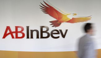 FILE - In this Thursday, March 3, 2011 file photo, a man walks past the AB InBev logos, in Leuven, Belgium. AB Inbev, the world's biggest brewer with brands like Budweiser and Corona, is selling its unit in Australia to reduce debt after it decided against listing shares in Asia. The company said Friday, July 19, 2019 it is selling Carlton & United Breweries for $16 billion AUD ($11.3 billion) to Japanese brewing rivals Asahi Group. (AP Photo/Yves Logghe, file)