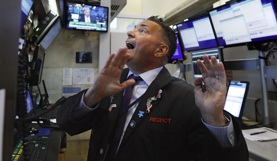 FILE - In this July 1, 2019, file photo trader Jonathan Muller works in his booth on the floor of the New York Stock Exchange. The U.S. stock market opens at 9:30 a.m. EDT on Friday, July 19. (AP Photo/Richard Drew, File)