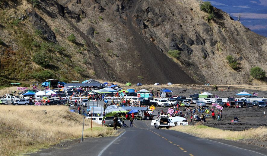 This photo provided by the Hawaii Department of Land and Natural Resources (DLNR) shows people who are against the construction of a Hawaii telescope continuing to block the roadway to the top of Mauna Kea, a mountain considered sacred by some Native Hawaiians, as the protest entered its fourth day Thursday, July 18, 2019. The action Thursday comes a day after 33 people were arrested, many of them elderly. Activists have fought the $1.4 billion Thirty Meter Telescope in courts and on the streets for years, but the latest protest could be their final stand as they run out of legal options. (Hawaii DLNR via AP)