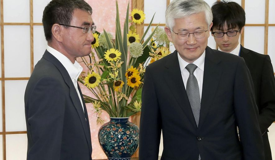Japan's Foreign Minister Taro Kono meets with South Korean Ambassador to Japan Nam Gwan Pyo, front right, at foreign ministry in Tokyo Friday, July 19, 2019. Japan has summoned South Korea's ambassador to protest Seoul's refusal to join in an arbitration panel to settle a dispute over World War II labor. (Masanobu Kumagai/Kyodo News via AP)