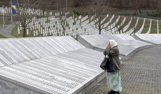 In this Wednesday, March 20, 2019, file photo, a woman prays at the Potocari memorial center for victims of the Srebrenica genocide, in Potocari, Bosnia and Herzegovina. The Dutch Supreme Court is ruling Friday, July 19, 2019, in a long-running legal battle over whether the Netherlands can be held liable in the deaths of more than 300 Muslim men who were murdered by Bosnian Serb forces during the 1995 Srebrenica massacre. (AP Photo/Marko Drobnjakovic, File)