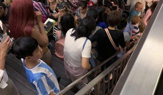 Commuters fill the stairs and line the platform at a New York City subway station as train service on seven lines came to a halt, Friday, July 19, 2019 in New York. The Metropolitan Transportation Authority blames the suspension on a network communications problem. (Kenneth Ferrone via AP)