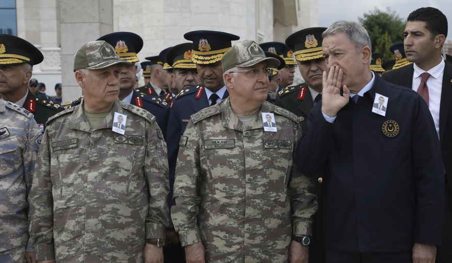 Turkey's Defense Minister Hulusi Akar, right, speaks with army's top commanders during the funeral prayers of Osman Kose, a 38-year-old Turkish diplomat killed in Iraq, in Ankara, Turkey, Thursday, July 18, 2019. A gunman opened fire inside a restaurant in the northern Iraqi city of Irbil on Wednesday, killing a Turkish diplomat working at Ankara's consulate, Turkey's state-run news agency and Iraqi media said.(AP Photo/Burhan Ozbilici)