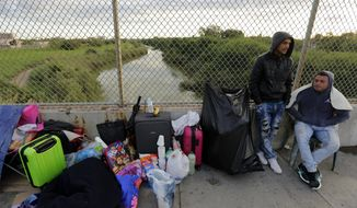 "FILE - In this Nov. 2, 2018, file photo, Yenly Morales,left, and Yenly Herrera, right, immigrants from Cuba seeking asylum in the United States, wait on the Brownsville and Matamoros International Bridge in Matamoros, Mexico. The U.S. government will expand its policy requiring asylum seekers to wait outside the country in one of Mexico's most dangerous cities. According to officials for two congressional Democrats, the Department of Homeland Security says it will implement its ""Migrant Protection Protocols"" in Brownsville, Texas, across the border from Matamoros, Mexico. Matamoros is in Mexico's Tamaulipas state, which the U.S. government warns citizens not to visit due to violence and kidnappings.(AP Photo/Eric Gay, File)"