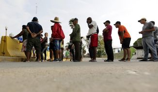 In this April 30, 2019, photo, migrants seeking asylum in the United States line up for a meal provided by volunteers near the international bridge in Matamoros, Mexico. (AP Photo/Eric Gay) **FILE**