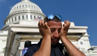 """A Capitol Hill police officer wipes sweat from his eyes as he stands his post on the West side of Capitol Hill in Washington, Saturday, July 20, 2019. The National Weather Service said """"a dangerous heat wave"""" was expected to break record highs in some places, particularly for nighttime. (AP Photo/Susan Walsh)"""