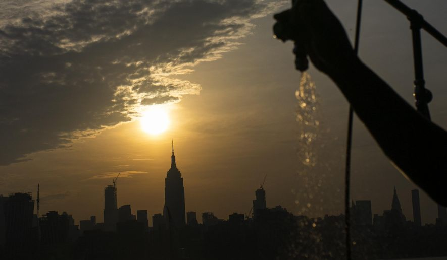 The sun rises over New York City and the Empire State Building while a man sprays water at Pier A on Saturday, July 20, 2019 in Hoboken, N.J. Temperatures in the high 90s are forecast for Saturday and Sunday with a heat index well over 100. Much of the nation is also dealing with high heat.   (AP Photo/Eduardo Munoz Alvarez)