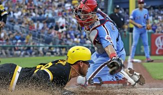 Pittsburgh Pirates starting pitcher Joe Musgrove, left, scores past the tag attempt by Philadelphia Phillies catcher J.T. Realmuto during the third inning of a baseball game in Pittsburgh, Saturday, July 20, 2019. Musgrove scored on a single by Pirates' Bryan Reynolds off Phillies starting pitcher Zach Eflin. (AP Photo/Gene J. Puskar)