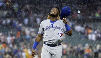 Toronto Blue Jays' Vladimir Guerrero Jr., with his glove tucked inside his uniform, walks off the field after a rain delay was called during the fourth inning of a baseball game against the Detroit Tigers, Saturday, July 20, 2019, in Detroit. (AP Photo/Duane Burleson)