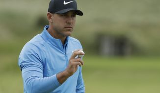 Brooks Koepka of the United States acknowledges the crowd after putting on the 12 the green during the third round of the British Open Golf Championships at Royal Portrush in Northern Ireland, Saturday, July 20, 2019.(AP Photo/Matt Dunham)