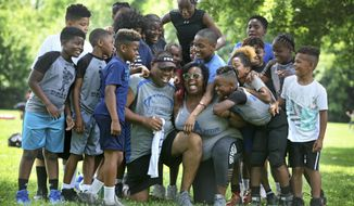 In a June 29, 2019 photo, during a break in an afternoon football practice, Michael and Maree Whitlow are showered with hugs by the kids in their Inspring Children to Excellence program. The couple felt like they had lost of their own children when 14-year-old Jaykwon Sharp was shot and killed; he had been part of the Columbus Inspiring Children to Excellence football program that the Whitow's founded.  (Doral Chenoweth III/The Columbus Dispatch via AP)