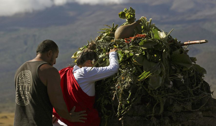 In this Sunday, July 14, 2019, file photo, Native Hawaiian activists pray at the base of Hawaii's Mauna Kea, background. For activists who say they're protecting Mauna Kea, the fight against the proposed Thirty Meter Telescope is a boiling point in Hawaiian history: the overthrow on the Hawaiian kingdom, battles over land, water and development and questions about how the islands should be governed. (AP Photo/Caleb Jones, File)