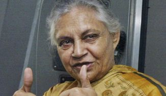 FILE - In this Oct. 26, 2006 file photo, Delhi state Chief Minister Sheila Dikshit displays the thumbs-up symbol as she rides a metro train in New Delhi, India. Dikshit, an Indian politician who was New Delhi's longest-serving chief minister, has died after a prolonged illness on Saturday, July 20, 2019. She was 81. (AP Photo/Rajesh Kumar Singh, File)
