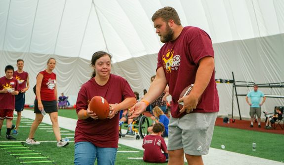 """Redskins rookie guard Wes Martin hands off a football at Washington's """"Special Olympics and Dreams for Kids Flag Football Kickoff"""" on Sunday, July 21 at the team's indoor facility in Ashburn, Virginia. (Photo courtesy of Stephanie Choi/Dreams for Kids)"""