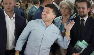 Ukrainian President Volodymyr Zelenskiy, center, gestures as he arrives at a polling station during a parliamentary election in Kiev, Ukraine, Sunday, July 21, 2019. Ukrainians are voting in an early parliamentary election in which the new party of President Volodymyr Zelenskiy is set to take the largest share of votes. (AP Photo/Evgeniy Maloletka)