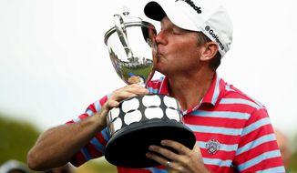 Jim Herman kisses the trophy after winning the PGA Barbasol Championship golf tournament at Keene Trace Golf Club's Champions Course in Nicholasville, Ky., Sunday, July 21, 2019. (Alex Slitz/Lexington Herald-Leader via AP)
