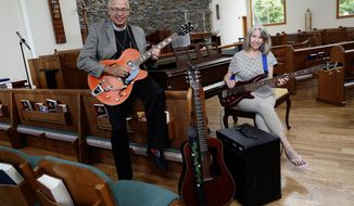 In a Sunday, July 7, 2019 photo, Rev. Dr. Stephen Smith sits with his Reverend Guitars Pete Anderson PA-1 that was a gift from his congregation to celebrate his 15th anniversary with the St. Patrick's Episcopal Church of Dublin and music director Jennifer Bell, the bassist in his band, inside the sanctuary. (Adam Cairns/The Columbus Dispatch via AP)
