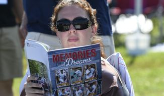 Roy Halladay fan Jacqueline Sarricchio of Bellmar, N.J., reads a program while waiting for the start of the National Baseball Hall of Fame induction ceremony at the Clark Sports Center on Sunday, July 21, 2019, in Cooperstown, N.Y. (AP Photo/Hans Pennink)