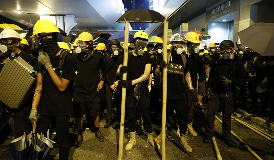 Protesters prepare to confront riot police in Hong Kong on Sunday, July 21, 2019. Protesters in Hong Kong pressed on Sunday past the designated end point for a march in which tens of thousands repeated demands for direct elections in the Chinese territory and an independent investigation into police tactics used in previous demonstrations. (AP Photo/Vincent Yu)