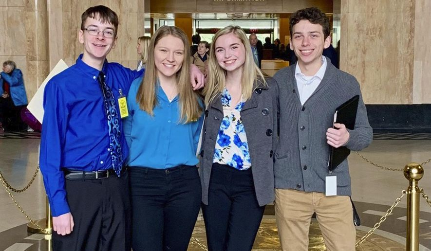 "In this Feb. 6, 2019, file photo provided by Providence Health & Services, from left, Sam Adamson, Lori Riddle, Hailey Hardcastle, and Derek Evans pose at the Oregon State Capitol in Salem, Ore. The teens introduced legislation to allow students to take ""mental health days"" as they would sick days in an attempt to respond to a mental health crisis gripping the state. (Jessica Adamson/Providence Health & Services via AP)"