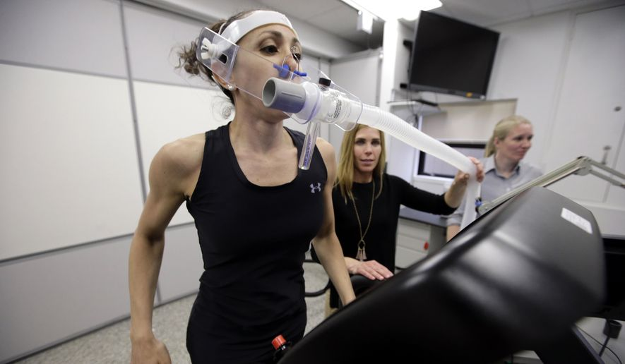 In this April 23, 2019, file photo, research scientist Leila Walker, left, is assisted by nutritional physiologist Holly McClung, center, as they demonstrate equipment designed to evaluate fitness levels in female soldiers, not shown, who have joined elite fighting units such the Navy Seals, at the U.S. Army Research Institute of Environmental Medicine, at the U.S. Army Combat Capabilities Development Command Soldier Center, in Natick, Mass. (AP Photo/Steven Senne)