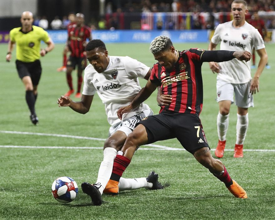 Atlanta United forward Josef Martinez, right, and D.C. United defender Donovan Pines, left, battle for the ball in front of the D.C. United goal during the first half in a soccer match on Sunday, July 21, 2019, in Atlanta. (Curtis Compton/Atlanta Journal-Constitution via AP)