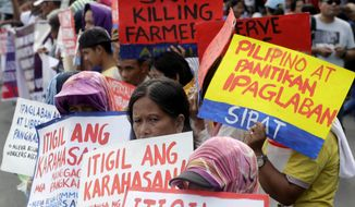 Protesters display placards as they prepare to march closer to the Philippine Congress to protest the 4th State of the Nation (SONA) address by President Rodrigo Duterte Monday, July 22, 2019 in suburban Quezon city, northeast of Manila, Philippines. Duterte is facing criticisms about his alleged closeness with China as well as the thousands of killings in his so-called war on drugs. (AP Photo/Bullit Marquez)