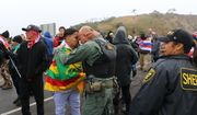 In this Monday, July 22, 2019, photo provided by the State of Hawaii, Mauna Kea law enforcement personnel interact with protesters blocking a road to the summit of Mauna Kea, a site considered sacred in Hawaii. Scientists want to build a telescope atop Mauna Kea because it is one of the best sites in the world for viewing the skies. The observatory would join 13 other telescopes already at the summit, though five are due to be decommissioned in a concession to telescope opponents. The Hawaii Supreme Court upheld the permit in 2018. (Dan Dennison/State of Hawaii via AP)