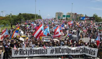 Thousands of Puerto Ricans gather for what many are expecting to be one of the biggest protests ever seen in the U.S. territory, with irate islanders pledging to drive Gov. Ricardo Rossello from office, in San Juan, Puerto Rico, Monday, July 22, 2019. Protesters are demanding Rossello step down for his involvement in a private chat in which he used profanities to describe an ex-New York City councilwoman and a federal control board overseeing the island's finance.(AP Photo/Dennis M. Rivera Pichardo)