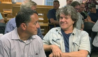 Michael Lang, right, Woodstock 50 co-producer and co-founder, sits in Vernon Town Hall before a planning board hearing in Vernon, N.Y., for his appeal to grant a permit for the Woodstock 50 music festival. (Edward Harris/Observer-Dispatch via AP)