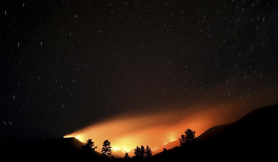 Pockets wildfires within the Museum fire create an ocean of light lapping at the slopes of the San Francisco Peaks as the fire burns Sunday, July 21, 2019, in Flagstaff, Ariz. (Jake Bacon/Arizona Daily Sun via AP)