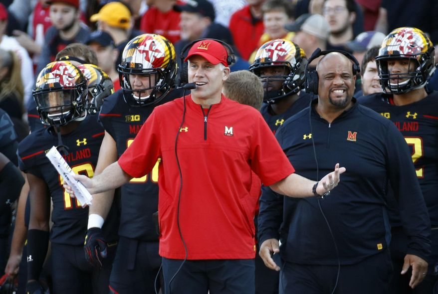 In this Oct. 14, 2017, file photo, Maryland head coach DJ Durkin, center, stands on the sideline in the first half of an NCAA college football game against Northwestern in College Park, Md. The Atlanta Falcons have brought in former Maryland coach DJ Durkin to serve as a guest coach during training camp, drawing immediate scrutiny over the wisdom of taking on someone who was fired from his previous job after a player's death. This is the first coaching stint for Durkin since he was dismissed by the Terrapins last October. (AP Photo/Patrick Semansky, File) **FILE**