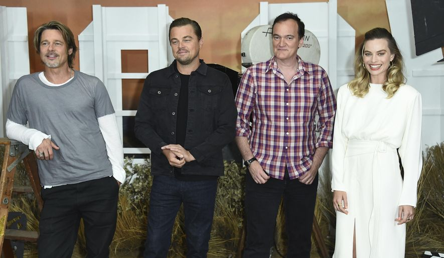 """FILE - In this July 11, 2019 file photo, Brad Pitt, from left, Leonardo DiCaprio, Quentin Tarantino and Margot Robbie attend the photo call for """"Once Upon a Time in Hollywood"""" at the Four Seasons Hotel in Los Angeles. The film opens on July 26. (Photo by Jordan Strauss/Invision/AP, File)"""