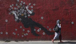 A woman walks past a mural in a sidewalk in downtown Tehran, Iran, Sunday, July 21, 2019. (AP Photo/Vahid salemi)