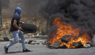 A Palestinian burns tires during clashes with Israeli forces near the West Bank city of Ramallah, Wednesday, July 17, 2019, as they protested a death of Palestinian in an Israeli jail. (AP Photo/Majdi Mohammed)