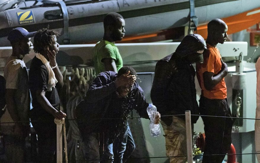 A migrants splashes water on his face as he disembarks with others from an Italian Guardia di Finanza finance police boat at the Sicilian port of Pozzallo, southern Italy, early Tuesday, July 9, 2019. According to reports 53 migrants were rescued in the Sicilian Channel by an Italian Coast Guard patrol vessel, but six of them were immediately transferred to Lampedusa due to medical conditions. (Ciccio Ruta/ANSA via AP)