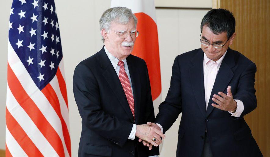 Japanese Foreign Minister Taro Kono, right, escorts U.S. National Security Adviser John Bolton, prior to their meeting in Tokyo Monday, July 22, 2019. (AP Photo/Eugene Hoshiko)