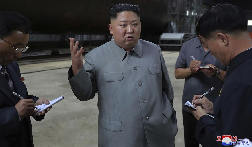 "In this undated photo provided on Tuesday, July 23, 2019, by the North Korean government, North Korean leader Kim Jong-un, center, speaks while inspecting a newly built submarine to be deployed soon, at an unknown location in North Korea. North Korean state media's report on Tuesday comes days after North Korea said it may lift its 20-month suspension of nuclear and missile tests to protest expected military drills between the United States and South Korea. Independent journalists were not given access to cover the event depicted in this image distributed by the North Korean government. The content of this image is as provided and cannot be independently verified. Korean language watermark on image as provided by source reads: ""KCNA"" which is the abbreviation for Korean Central News Agency. (Korean Central News Agency/Korea News Service via AP)"