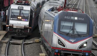 FILE - In this March 12, 2016, file photo, an Amtrak train passes a New Jersey Transit train stopped to discharge and board passengers at Elizabeth train station in Elizabeth, N.J., along Amtrak's Northeast Corridor. A review conducted on behalf of New Jersey Transit and Amtrak Rail concludes that delays of five hours or more for commuters between New Jersey and New York have occurred about 17 times per year in recent years. (AP Photo/Mel Evans, File)