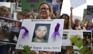 In this Aug. 17, 2018, file photo, Christine Gagnon, of Southington, Conn., holds a sign during a protest with others who have lost loved ones to OxyContin and opioid overdoses, outside the Purdue Pharma headquarters in Stamford, Conn. Gagnon lost her son Michael 13 months earlier. Nearly ten years ago, the blockbuster painkiller OxyContin was reformulated to discourage abuse by snorting and injecting, but it's unclear whether the harder-to-abuse format has decreased cases of addiction, overdose and death. (AP Photo/Jessica Hill, File)