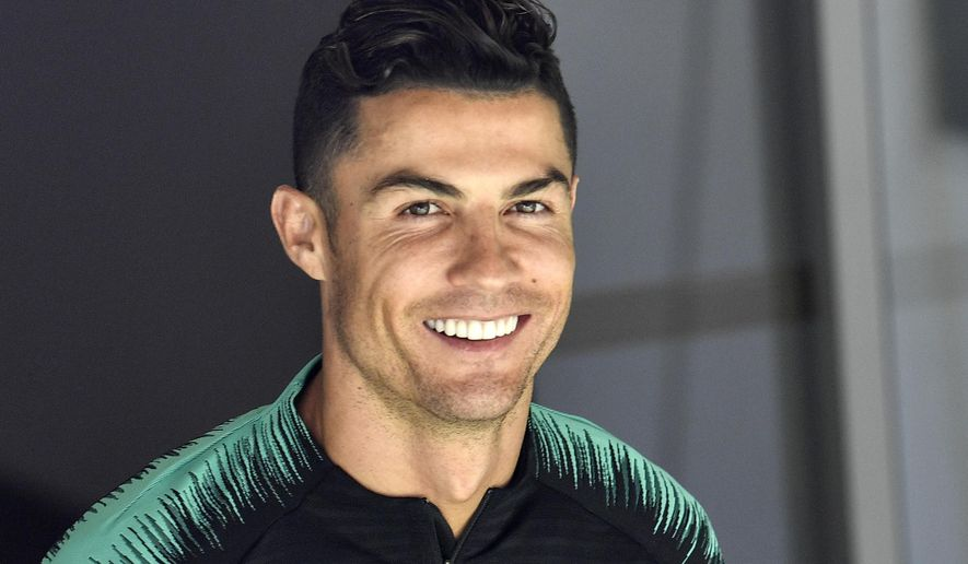 FILE - In this June 8, 2019, file photo, Portugal's Cristiano Ronaldo smiles when he arrives to a training session at the Bessa stadium in Porto, Portugal. Soccer star Cristiano Ronaldo won't face criminal charges after a woman accused him of raping her at a Las Vegas Strip resort in 2009.  Prosecutor Steve Wolfson said in a statement Monday, July 22, 2019, that after reviewing a new police investigation, he determined that sexual assault claims can't be proven beyond a reasonable doubt and no charge will be filed. (AP Photo/Martin Meissner, File)